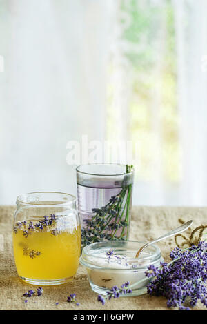 Materias orgánicas miel, azúcar blanco en frascos de vidrio, vidrio de agua aromatizada con flores de lavanda, de pie sobre la mesa con el cilicio. Estilo rústico, la luz del día