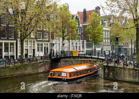 Canal Boat pasando bajo un puente en el Brouwersgracht, Amsterdam, Países Bajos, Europa