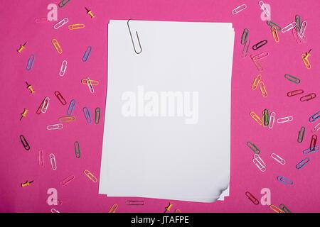 Vista superior de papeles en blanco y coloridos clips aislados en rosa