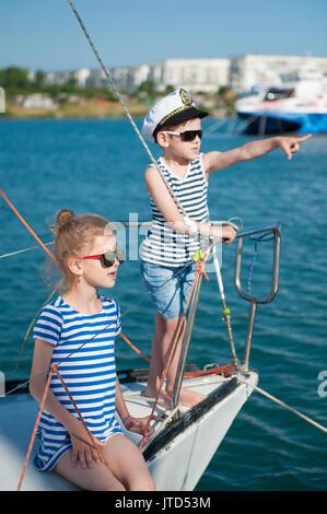 ... Happy cute kids a bordo del yate de lujo en verano soleado día en  puerto Foto 543c808a477