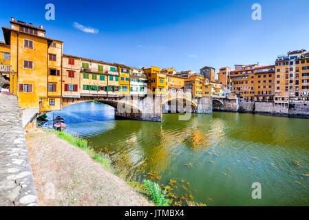 Florencia, la Toscana - Ponte Vecchio, el puente medieval sobre el río Arno sunlighted, Italia.