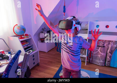 Chico, de 7 años, juega un juego de ordenador en 3-D, con un casco de realidad virtual, en su habitación niños,