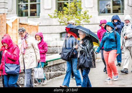 La Ciudad de Quebec, Canadá - 30 de mayo de 2017: Primer plano de grupo de viaje de gente caminando en Heavy Rain con sombrillas
