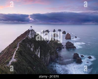 Nugget Point Lighthouse ofrece orientación sobre el camino a la ruptura en las lejanas nubes tormentosas. Nueva zelanda otago, Isla del Sur,.. El catlins.