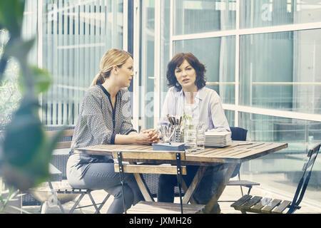Dos mujeres empresarias haber discusión durante el almuerzo de negocios fuera de la oficina