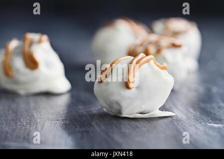 Trufas de chocolate blanco para Navidad o San Valentín aderezada con salsa de mantequilla de maní. Profundidad de campo extremas con el enfoque selectivo en c