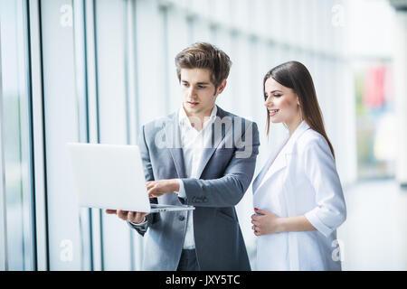 Pareja discutiendo en el portátil nuevo proyecto atanding contra en Office habitación con ventanas panorámicas Foto de stock