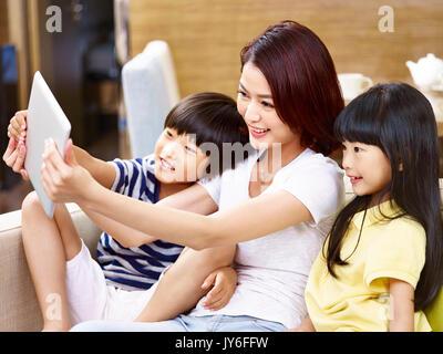 Joven madre asiática y niños sentados en el sofá tomando una tableta digital selfie, feliz y sonriente.