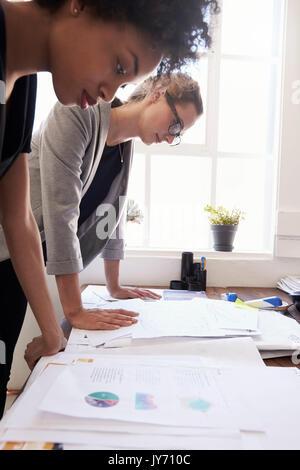 Dos mujeres empresarias estudiando los documentos en una oficina, vertical