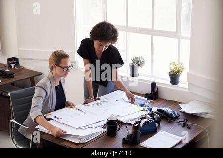 Dos jóvenes empresarias estudiando los documentos en una oficina.