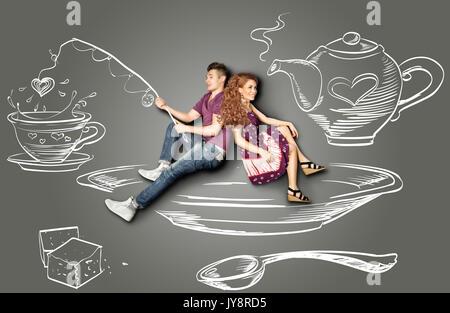 Feliz día de San Valentín historia de amor con la idea de una pareja romántica sentado en un platillo y la pesca en un vaso de agua contra el fondo de dibujos con tiza.