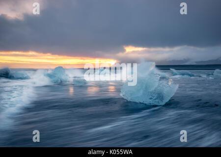 Bloque de hielo en la playa negra en la Laguna glaciar Jokulsarlon durante una puesta de sol, el este de Islandia, Europa