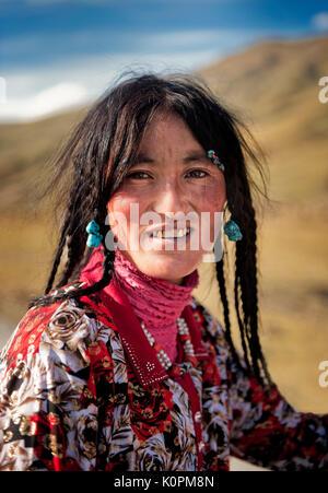 Una joven mujer tibetana vistiendo los accesorios tradicionales típicas de su grupo étnico, así como sus caninos Foto de stock