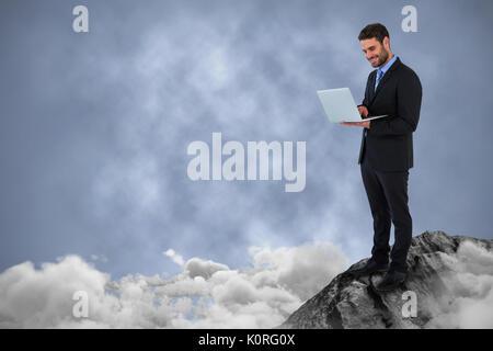 Empresario de pie mientras se utiliza equipo portátil contra el fondo oscuro