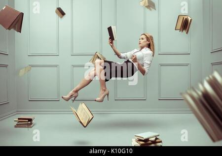 Una mujer relajada levanta en una habitación llena de libros de vuelo Foto de stock