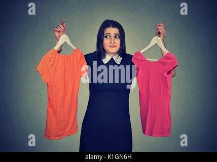Confundirse mujer elegir entre vestidos y no puede hacer la decisión.
