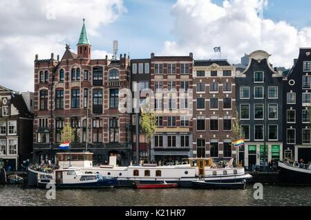 Amsterdam, Holanda - 27 de abril, 2017: Casas flotantes y viviendo barcazas en Binnenamstel canal contra casas de típica holandesa con pabellón de Países Bajos y