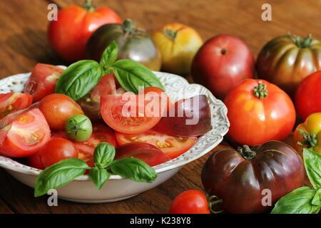 Colorida ensalada de tomates con albahaca y vinagre balsámico sobre fondo rústico de madera Foto de stock