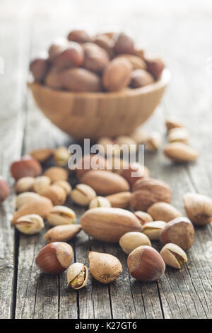 Los diferentes tipos de frutos secos en la cáscara de nuez. Las avellanas, nueces, almendras, nueces de nogal y los pistachos en la mesa de madera antigua.