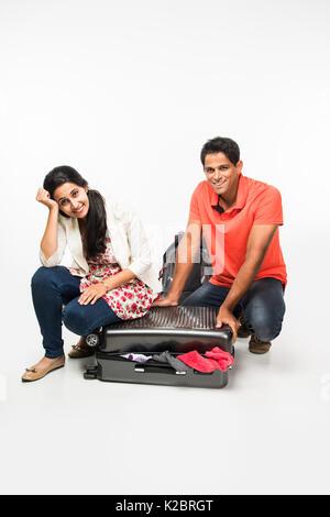Fotos de pareja joven indio embalaje para vacaciones, intentando cerrar la maleta llena de ropa, sentados aislado sobre fondo blanco.