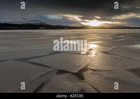 Loch Morlich congelados al atardecer con montañas en la distancia, el Parque Nacional de Cairngorms, Escocia (Reino Unido), enero de 2015.