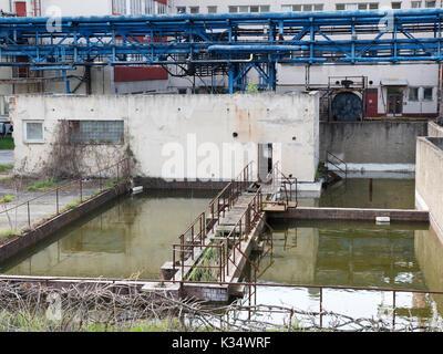 Construcción de fábrica con depósito de agua. Luz de día, nublado cielo, el sitio de químicos desde los 70s a 90s. Productos químicos para la industria farmacéutica.