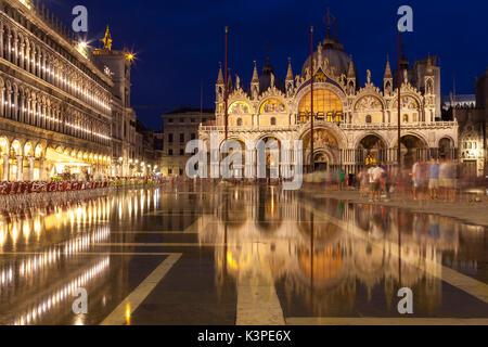 La Basílica de San Marcos de noche iluminado durante la hora azul se reflejan en las quietas aguas de acqua alta en Piazza San Marco, Venecia, Véneto, Italia con