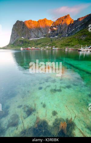 Sol de Medianoche en el pueblo de pescadores rodeado de aguas cristalinas y las cimas del condado de Nordland Reine de las Islas Lofoten Noruega del Norte de Europa