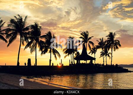 Siluetas de palmera durante la puesta de sol en la playa de Kota Kinabalu, Sabah, Borneo, Malasia. Foto de stock