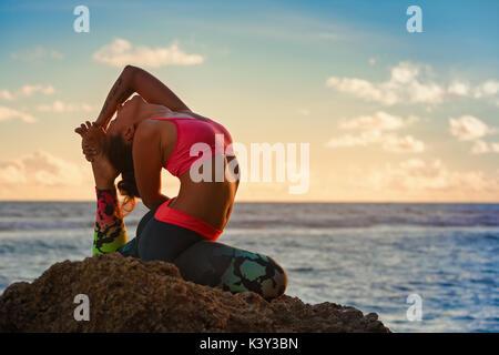 La meditación sobre el fondo del cielo al atardecer. Activa joven mujer sentada en pose de yoga en la playa rock, estiramiento para mantenerse en forma y salud. Estilo de vida saludable, fitness