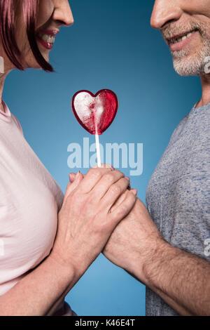 Captura recortada de la pareja de ancianos tomados de la mano con la piruleta en forma de corazón