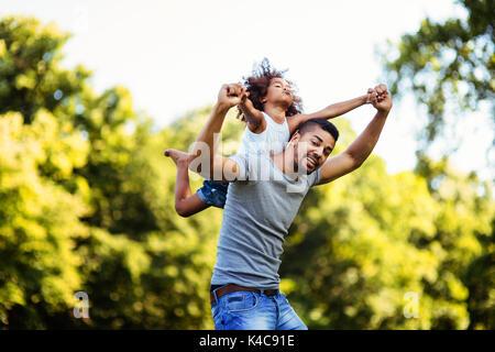 Retrato de joven padre llevar a su hija en la espalda