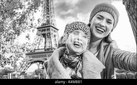 Escapadas de otoño en París con la familia de la madre y el niño feliz viajeros en terraplén cerca de la torre Eiffel en París, Francia, teniendo selfie mientras está sentado o