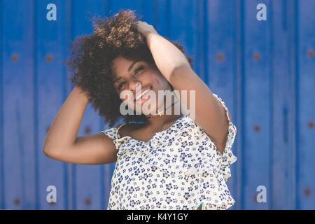 Retrato de mujer afro americana feliz tomados de las manos en la cabeza. Foto de stock