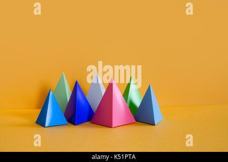 Diseño minimalista colorida composición geométrica abstracta. Prisma pirámide tridimensional objetos rectangulares en papel amarillo de fondo. Rosa Azul Gris Verde Color figuras sólidas, enfoque suave.