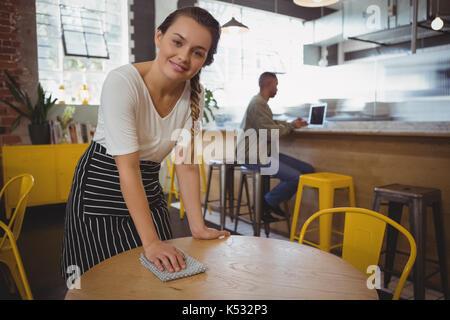 Retrato de joven camarera en el café la mesa de limpieza