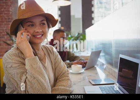 Mujer joven con portátil hablando por teléfono al contador en cafe Foto de stock