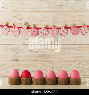 Los huevos de Pascua y decoración de Pascua, huevos de papel con una cinta rosa sobre un fondo de madera ligera. El enfoque selectivo.