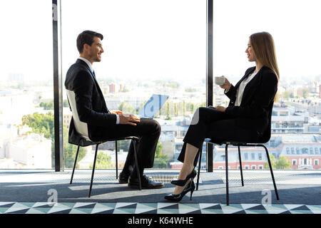 Dos jóvenes empresarios sentados junto a las ventanas panorámicas y hablando