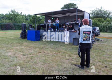 Banda toca en el escenario en un campo vacío en concierto con pequeña audiencia Foto de stock