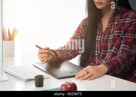 Creative mujer trabajando en la oficina creativa con ordenador y gadget o dispositivo en el escritorio, artista gráfico concepto de diseño.