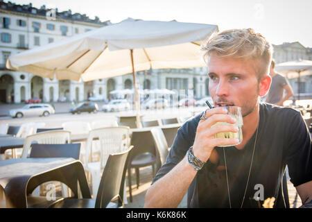 Apuesto hombre sentado en el café la celebración de vidrio