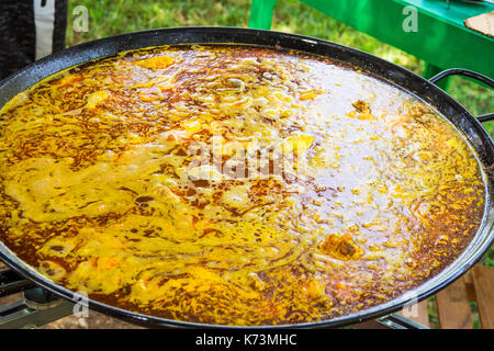 Proceso de cocinar paella española o jambalaya en sartén plana grande. Ingredientes carnes, arroz, legumbres, especias simmering en caldo de pollo con tomate sau