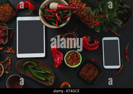 Sobrecarga de diversas especias con la tableta digital y móvil sobre fondo negro