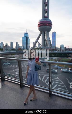 Mujer joven tomando selfie cerca del radio & Oriental Pearl TV Tower, famosa atracción turística situado en el nuevo Foto de stock