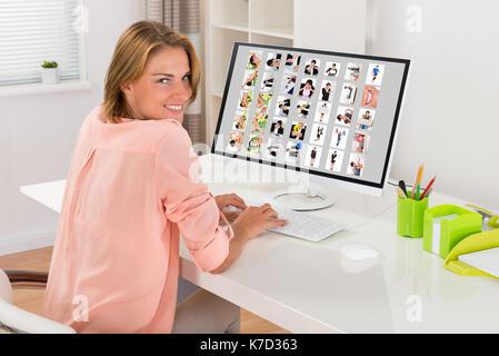 Feliz joven editora trabajar con fotos en el equipo de Office