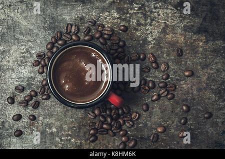 Taza de café con granos tostados sobre fondo de piedra, desde arriba