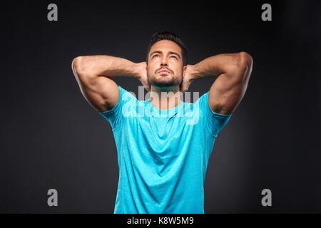 Un apuesto joven deportista con confianza permanente con los brazos por encima de su cabeza