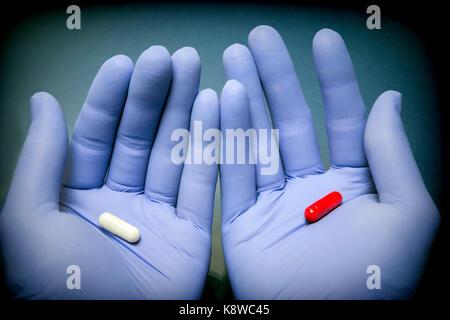 Blue-mano enguantada posee dos cápsulas en rojo y blanco, elija buenas o malas como concepto Foto de stock