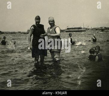 Antique c1920 fotografía, dos mujeres en el periodo de trajes de baño en un baño popular lago con botes en el fondo. Ubicación desconocida, probablemente de Nueva Inglaterra. Fuente: fotografía original.